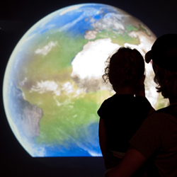 Father and daughter watching the NASA climate change exhibit