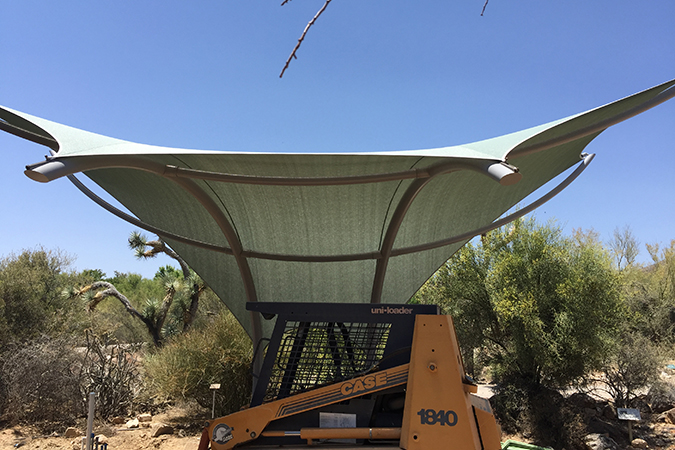 Exhibit construction continues under the newly erected shade structure
